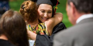 girl graduations hugging peer