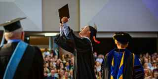 Photo of a student holding up his diploma in victory.