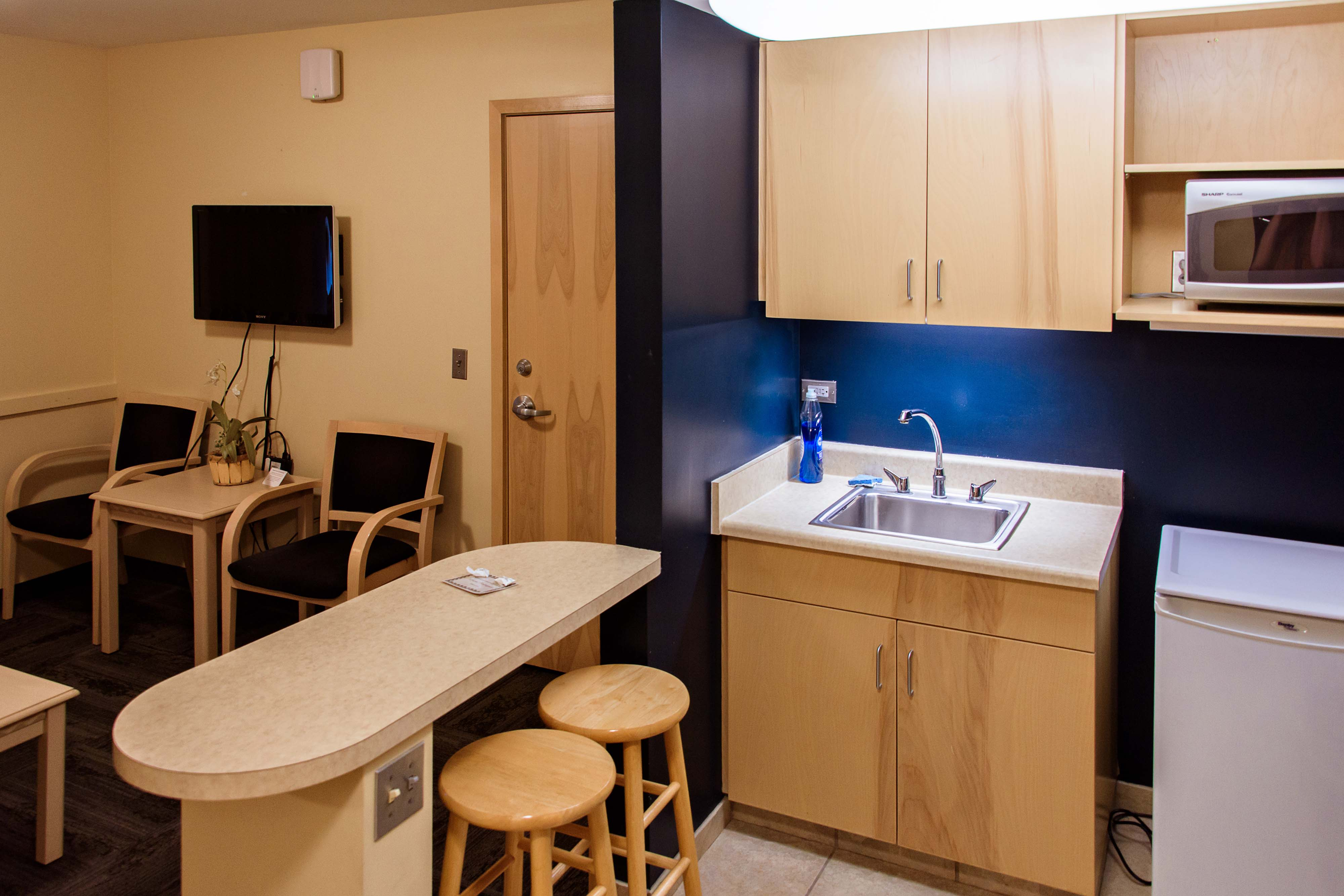An angle showing off the kitchen and its appliances in the Ortner Center's 1-bedroom suite