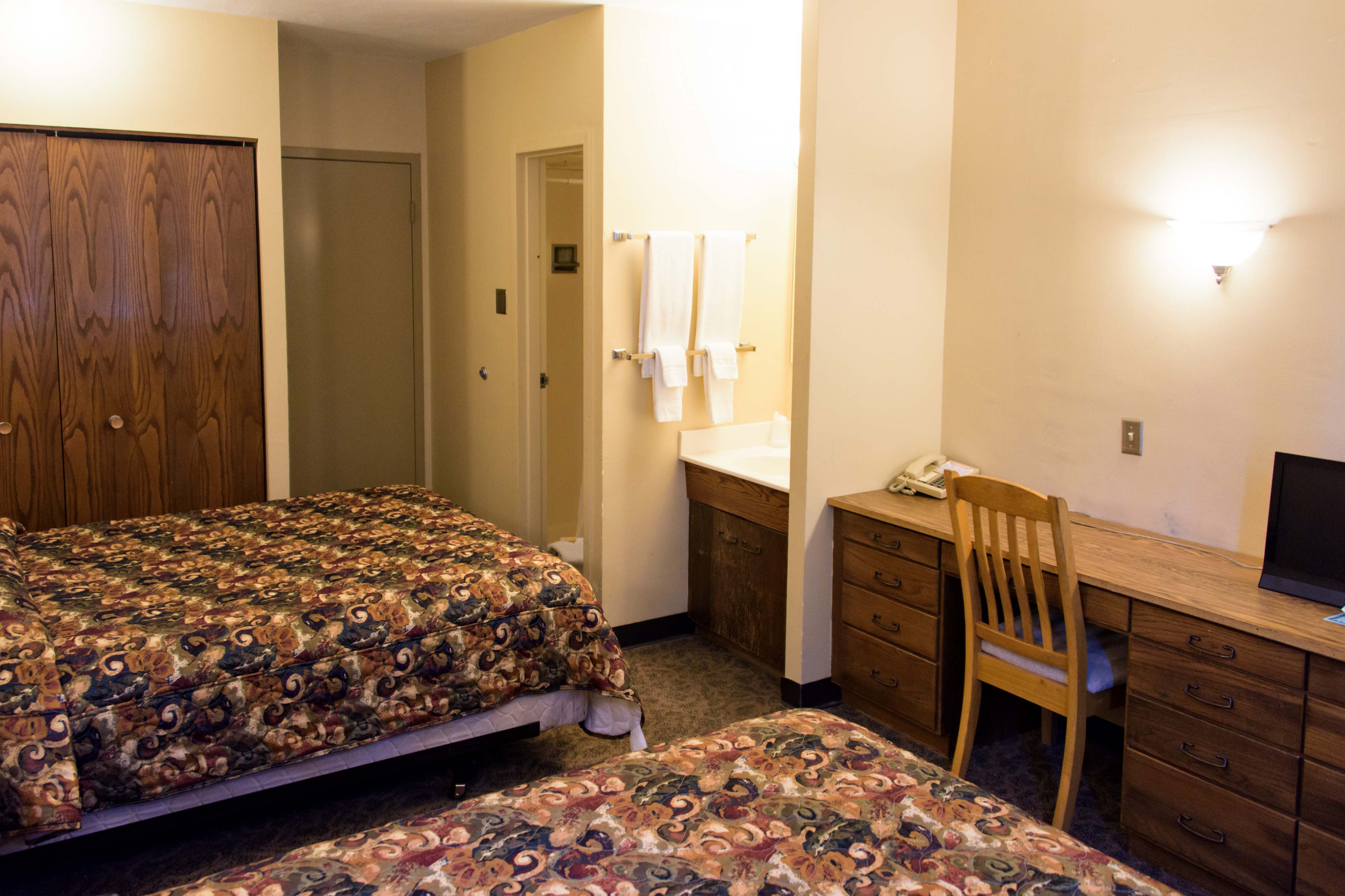 A view of Prescott Hall's standard guest room showcasing the beds, desk, and sink area