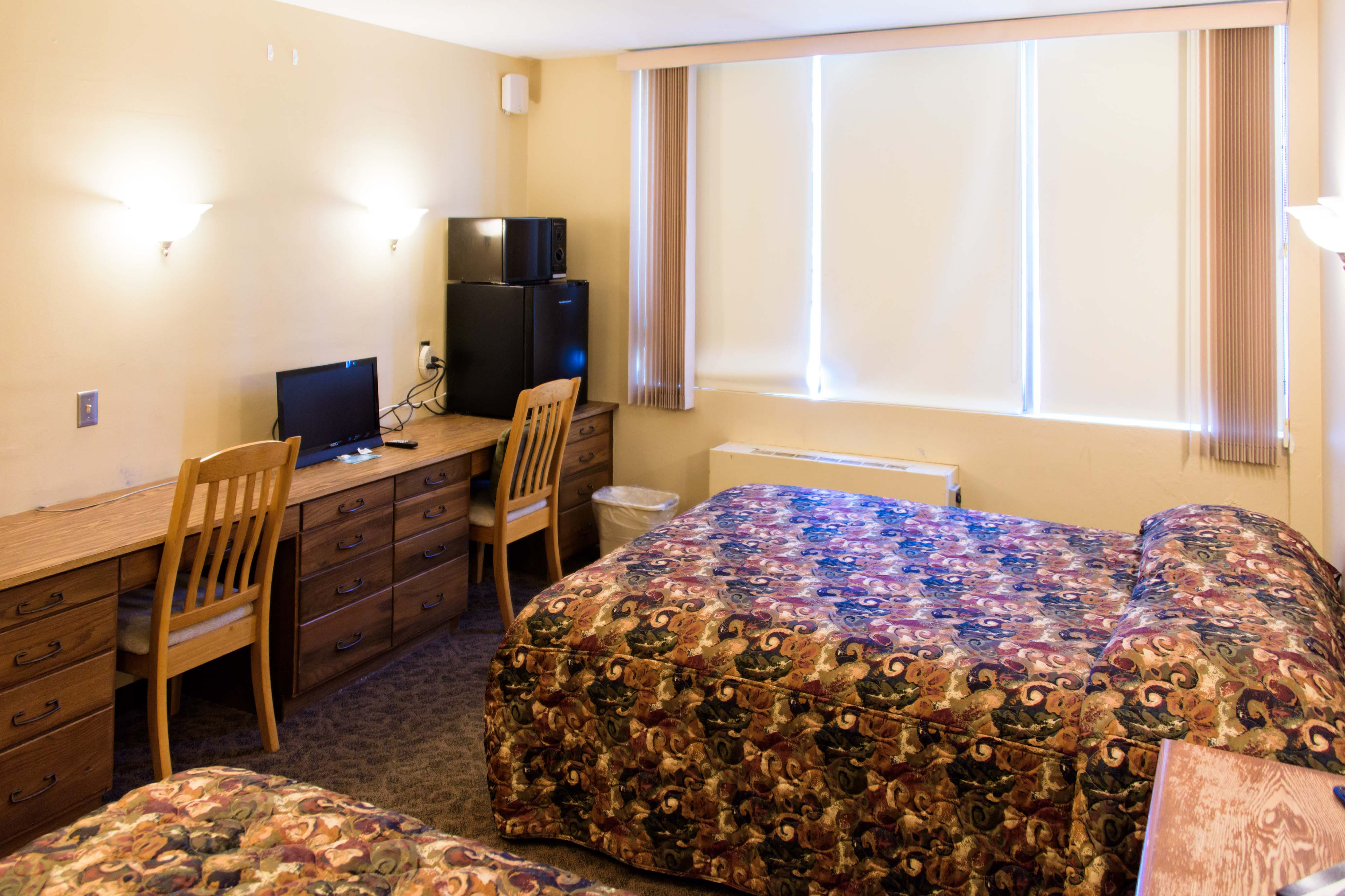 A view of Prescott Hall's standard guest room showcasing the beds, desk, TV, microwave, and fridge