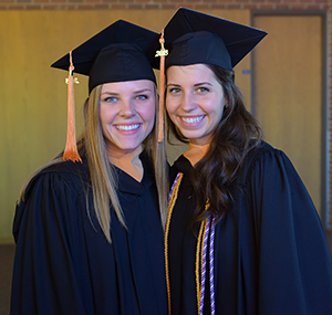 photo of Stephanie Grote and Hope Sajdak in graduation robes