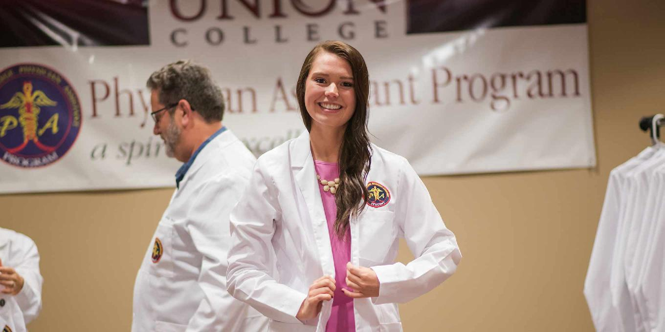 Photo of a PA student putting on her white coat.