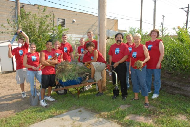 Photo of students and employees doing yard work with Jose Rojas during Project Impact.