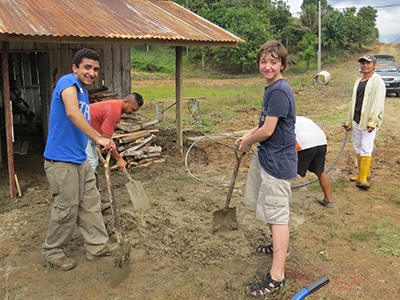 Photo: Students digging in mud.