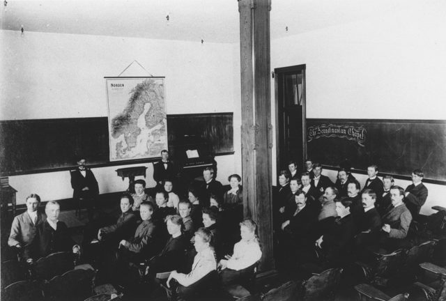 Old photo of students in a classroom with a map of Scandanavia