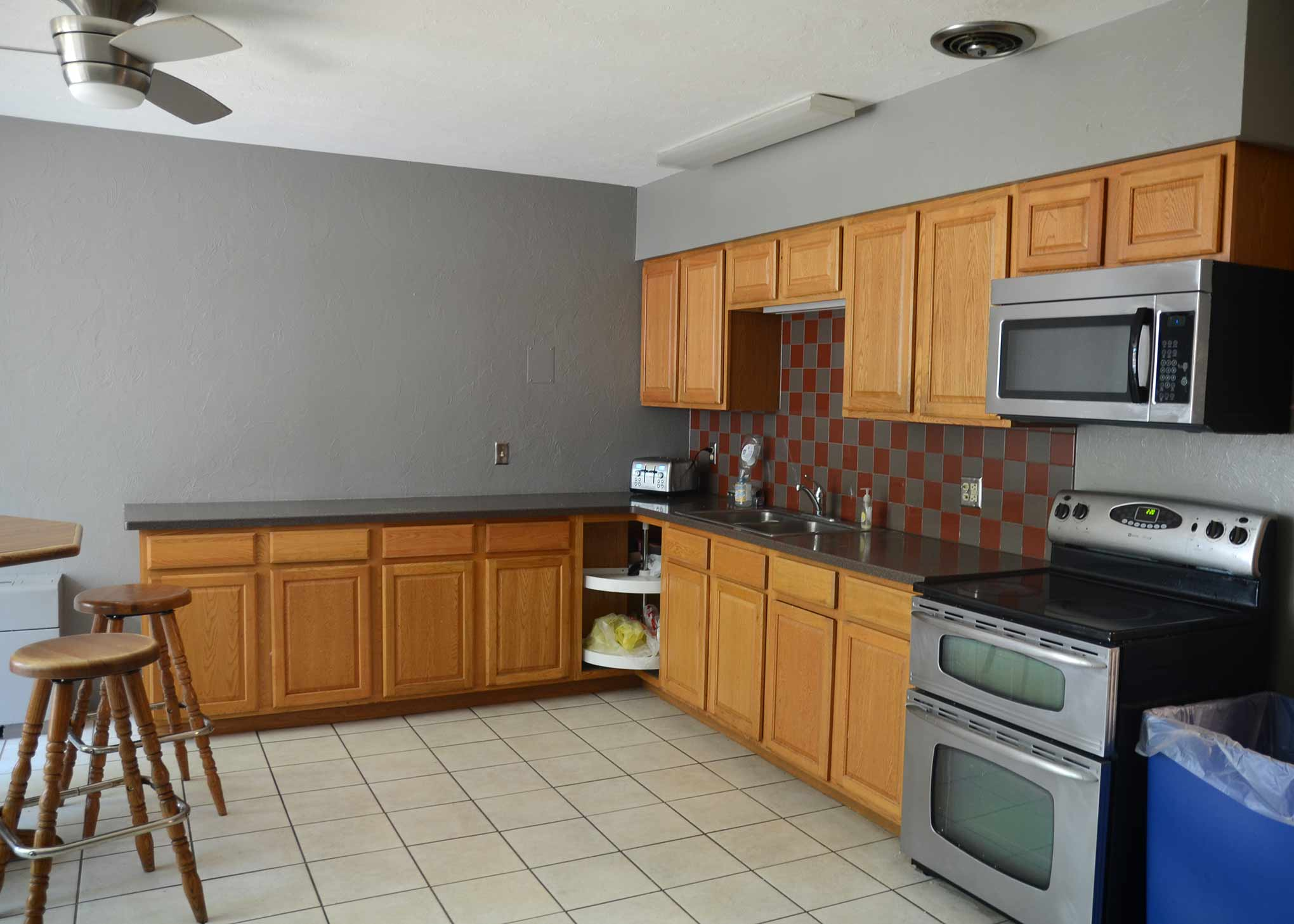 Rees Hall kitchen. Includes microwave, stove, refrigerator, sink, counter-space, cabinets, and tables.