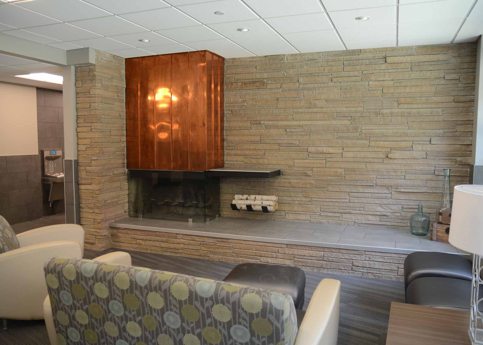 A part of the Rees Hall lobby that includes a fireplace and comfortable seating