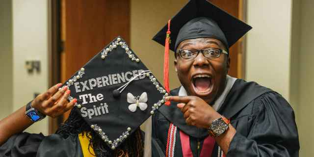 Photo of a student pointing to a graduation cap with Experience the Spirit written on it.