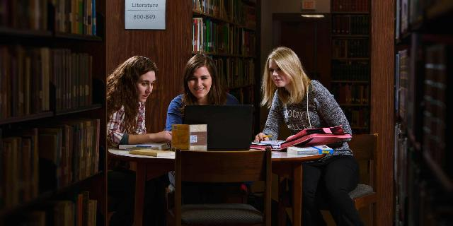 Photo of three students studying in the library.