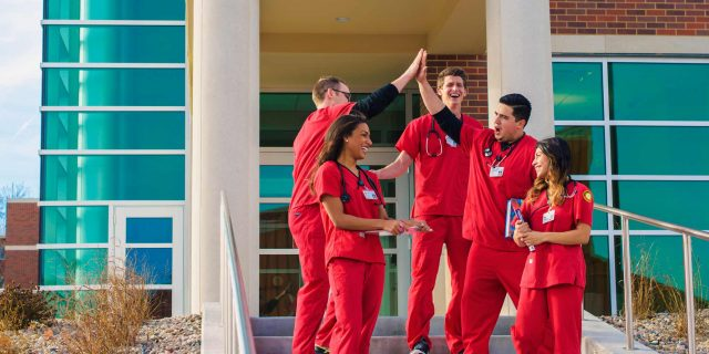 Photo of nursing students high fiving.