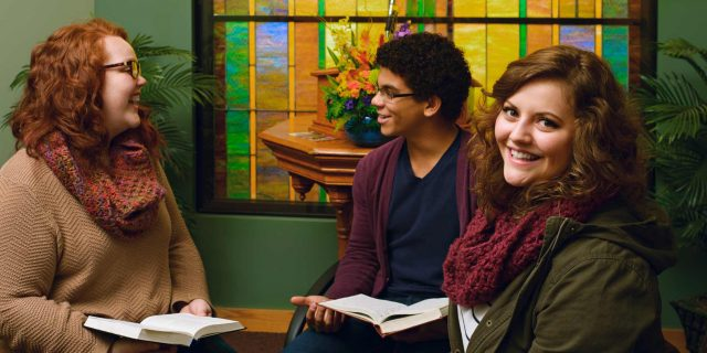 Photo of three students studying the Bible in a chapel.