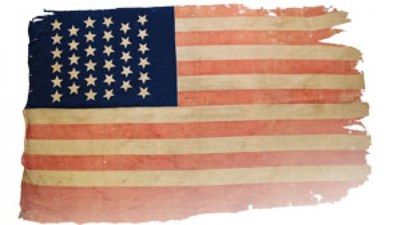 Photo of a slightly tattered American flag with 34 stars.