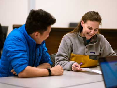 Photo of a tutor helping a student on a writing assignment.