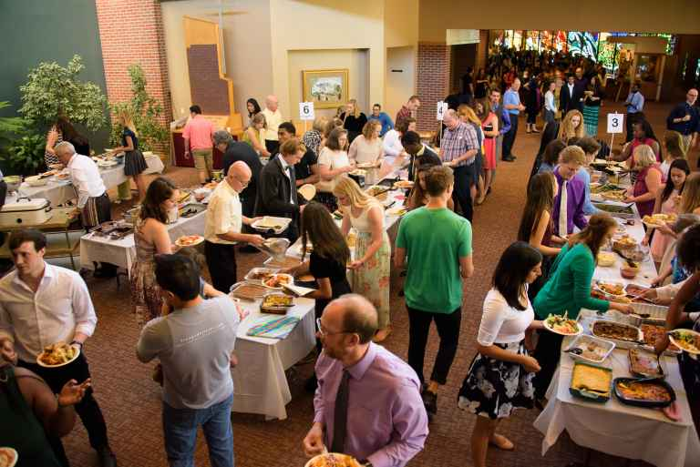 Students and the local Adventist community share a fellowship dinner.