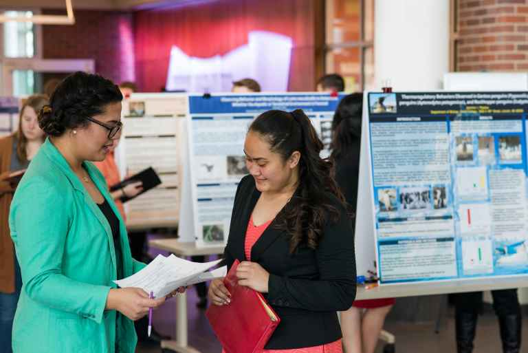Students present their research in the lobby of the Krueger Center.