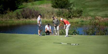 Photo of four men playing golf.