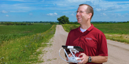 Photo of Seth McNeill piloting a drone over a cornfield.