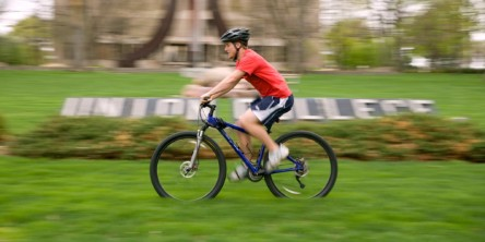 Photo of a student cycling with motion blur.