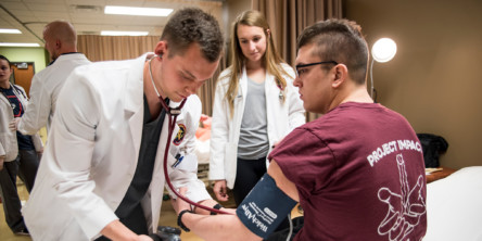 Photo of a PA student taking blood pressure.